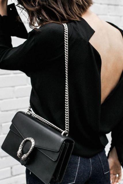 Mulher usando blusa decotada nas costas e bolsa preta.
