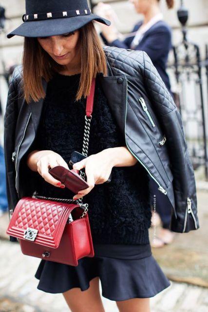 Bolsa vermelha, saia, blusa, jaqueta e chapéus pretos.