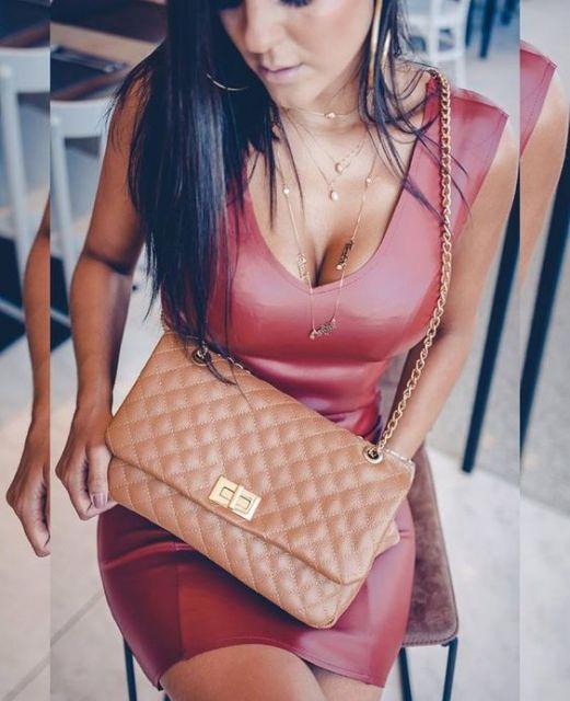 Vestido de couro vermelho e bolsa bege.