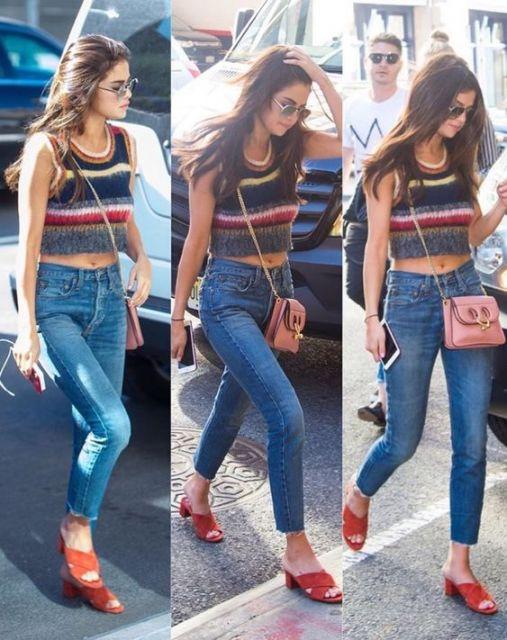 Selena Gomez com bolsa rosa, jeans e cropped.