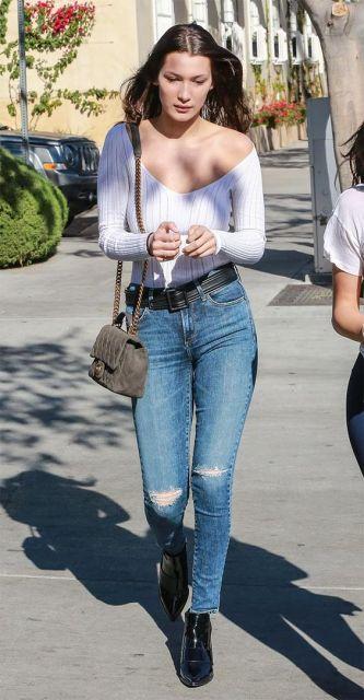 Bella Hadid usando calça jeans destroyed, body branco e bolsa.