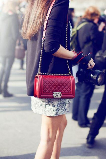 Bolsa vermelha combinada com saia estampada branca e blazer preto.